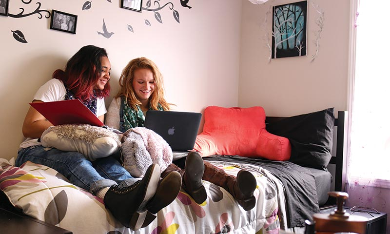 Two girls sitting on a bed, working on homework